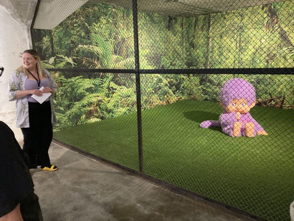 Anja Carr viser installasjon med et stort troll, gjerdet inn i et grønt landskap.